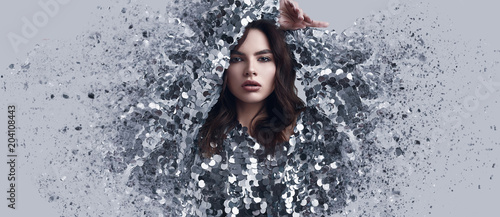 Wall mural Beautiful brunette woman in fashion dress of sequins with dispersion effect