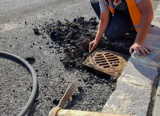 Road construction worker removing the asphalt from the residential house sewage shaft to move it.