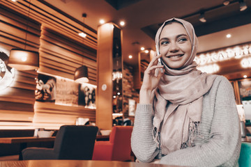 beautiful Muslim girl with a headscarf sitting in an oriental cafe, waiting for her food and talking on the phone