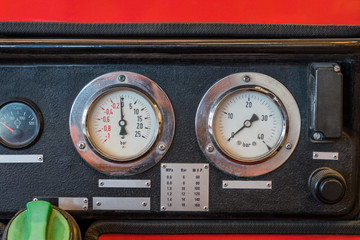 Close up of a black old worn panel with analog meters.
