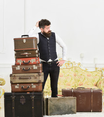 Macho elegant on tired face, exhausted at end of packing, leans on pile of vintage suitcases. Man with beard and mustache packed luggage, white interior background. Baggage and relocation concept.