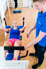 Female athlete and her physical therapist during exercise at workout equipment in health club