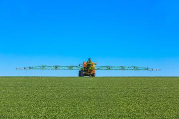Traktor besprüht junges Feld mit Glyphosat