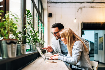 Smiling couple looking at laptop screen indoors. Discussing the good news.