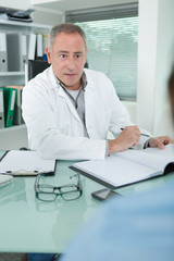 Medical practitioner with notebook talking to client