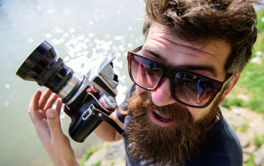 Man with beard and mustache wears sunglasses, water surface on background. Hipster on smiling face holds old fashioned camera. Tourist photographer concept. Guy shooting nature near river or pond.