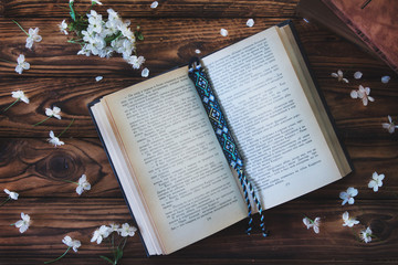 open book with bookmark on wooden background with white flowers