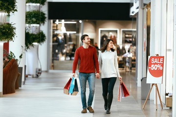 Couple Shopping. Happy Man And Woman With Bags