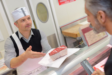 male butcher seving a male customer