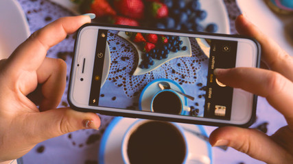 A girl or a woman takes a photo of food, breakfast, coffee, donuts, strawberries, coffee.