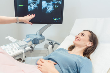 Woman at the gynecologist having ultrasonic examination as pregnancy test