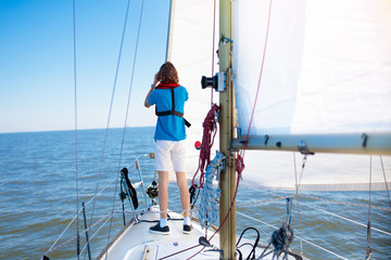 Young man sailing. Teenager boy on sea sail boat.