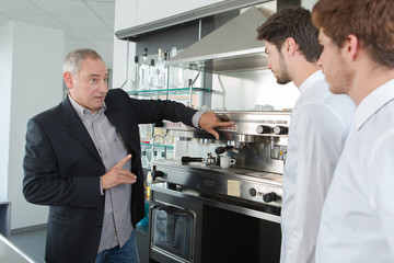 Manager showing coffee machine to two young waiters