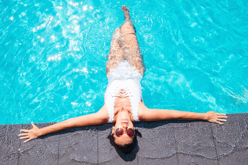 Woman in white swimsuit relax in swiming pool on luxury resort