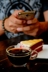 taking photo with black coffee and red velvet cake on dark wooden table with smartphone with man hand. for up to social network .