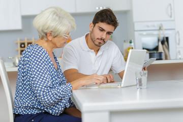 man teaches an elderly woman how to work using laptop