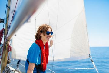 Young man sailing. Teenager boy on sea sail boat.