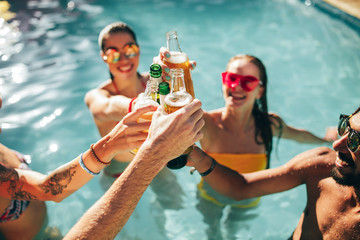 Friends enjoying and toasting drinks at pool party