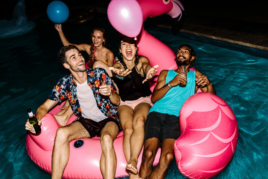 Group of friends partying in the swimming pool