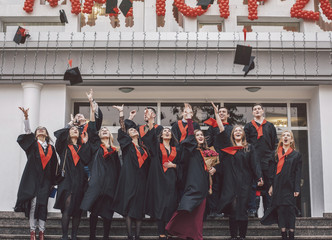 Low angle view of happy students wearing graduation gowns standing on steps by building