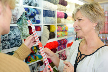Woman in craft shop looking at knitting needles