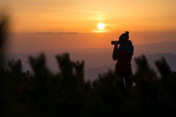 Young women photographer trying to capture the sunrise through her camera