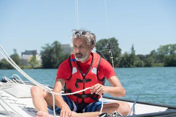 mature man enjoying sailing on a sunny day