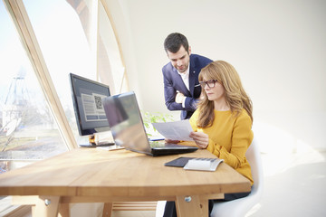 Young financial assistant businessman sitting in front of laptop and presenting his business plan to executive businesswoman. Group of business people working together at the office.