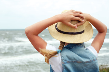 Happy child on a turquoise sea background. Back view. Horizontal photo