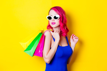 Young pink hair girl in blue dress with colored shopping bags. Portrait isolated on yellow background