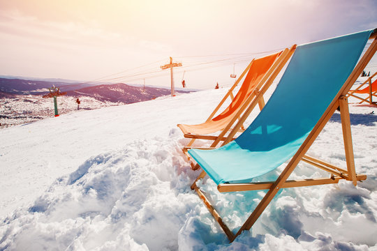 Chair relax lounges winter against blue sky with sun and mountains.