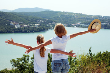Happy family traveling: mother and child daughter look at the mountains and sea.