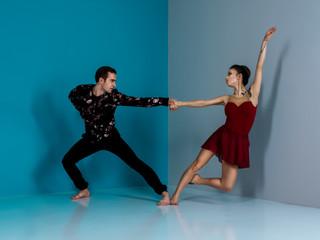 Modern ballet dancer couple in black trousers black in roses shirt and bordo dress performing art...