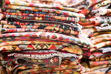 Stack of multicolored quality rugs  at carpet shop