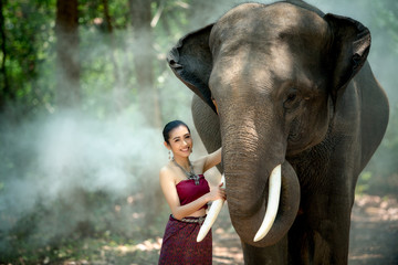 Asian woman enjoying with elephant at Chang Village Surin province Thailand.