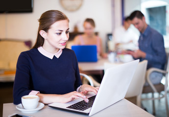 Positive woman using laptop and drinking coffee in cafe
