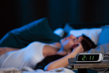 Photo of young woman with insomnia lying on bed next to clock