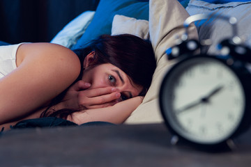 Portrait of brunette with insomnia lying on bed next to alarm clock at night