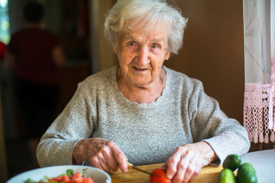 Elderly woman preparing vegetables for a salad.