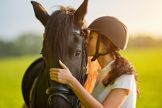 Young Woman kissing her horse at sunrise.