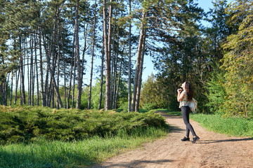 girl with camera taking pictures of nature in spring, beautiful forest and trees on a Sunny day