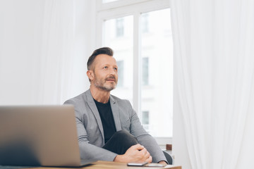 Thoughtful mature man sitting at office