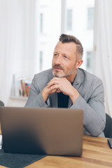 Mature man sitting in front of laptop