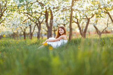 A portrait of a beautiful young girl with blue eyes in a white dress with dandelions in the garden with apple trees blosoming having fun and enjoying smell of flowering spring garden at the sunset