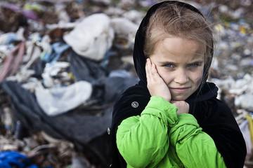 A beggar little girl in rags in a city dump close up