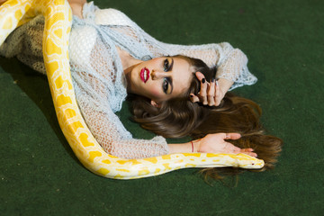 Beauty woman relax with albino python. Beauty model with makeup face and yellow snake.