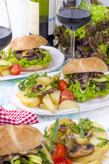 Delicious vegetarian burgers and potatoes for three. Lunch and wine. Light background and space for text.