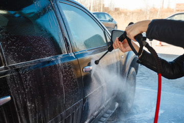 Girl washes a black SUV with a high-pressure car wash. Soap foam and water on the machine. Self-service car wash. A young woman washes the car in the street car wash in the fresh air.