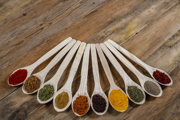 Assorted spices on wooden spoons. Delicious food ingredients.