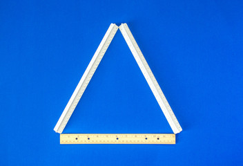 back to school- 3 measuring rulers forming a triangle isolated on a blue background with copy space